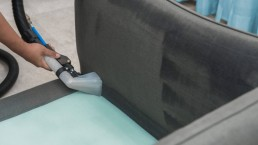 A close up image of a sofa being professionally cleaned